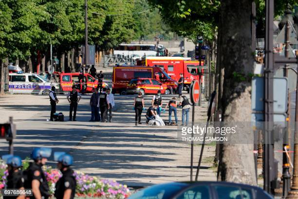 Graphic content / Judiciary Police Officers tend to the body of a man lying under a white sheet in a sealed off area of the ChampsElysees avenue in...