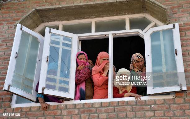 Graphic content / Kashmiri mourners look on during the funeral of taxi driver Ali Muhammad Dagga who died when when he and the car he was driving...