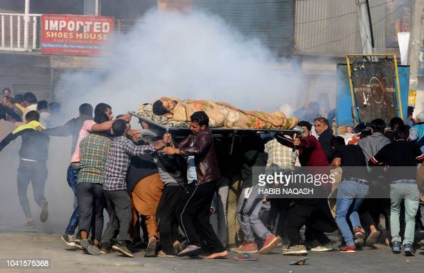 Graphic content / Kashmiri mourners raise slogans as they march with the body of the slain civilian Saleem Malik to the martyrs graveyard in Eidgah...