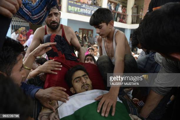 Graphic content / Kashmiri villagers carry a body of a youth Irshad Ahmed during a funeral procession at Kulgam south of Srinagar on July 7 2018...
