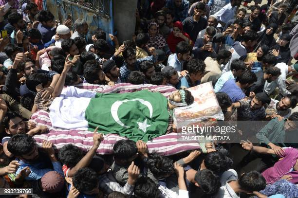 Graphic content / Kashmiri villagers carry a body of a youth Shakir during a funeral procession at Kulgam south of Srinagar on July 7 2018 Troops...