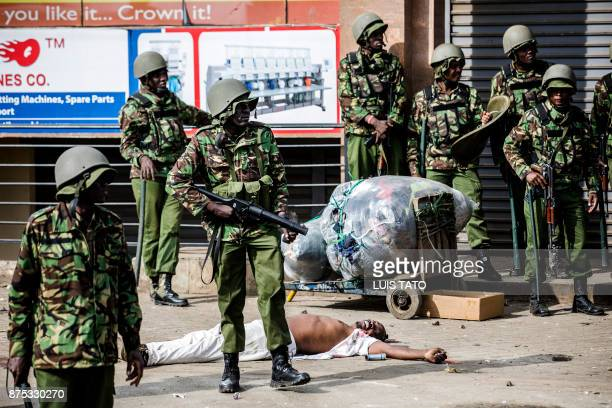 Graphic content / Kenya police officers surround the body of a man allegedly was shot dead by police during a demonstration by Kenya's opposition...