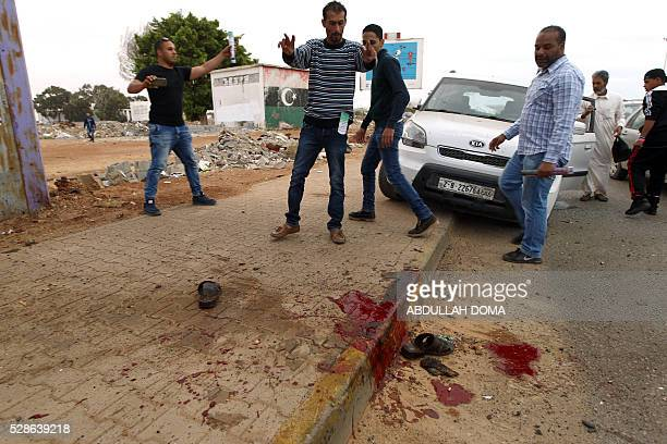 Graphic content / Libyans look at blood stains on the ground after shelling hit a demonstration in the eastern coastal city of Benghazi calling for...