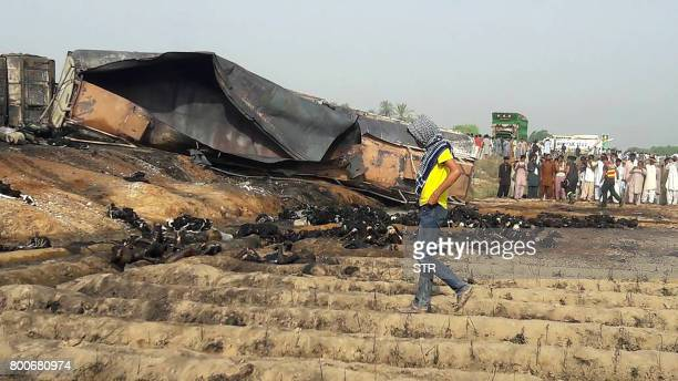Graphic content / Local residents look at burnt bodies after an oil tanker caught fire following an accident on a highway near the town of Ahmedpur...
