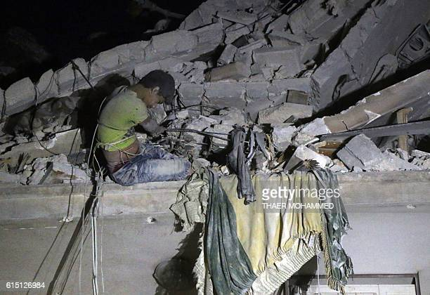 Graphic content / Maarouf a 12yearold Syrian boy waits to be rescued from the rubble of a building following a reported air strike on the the...