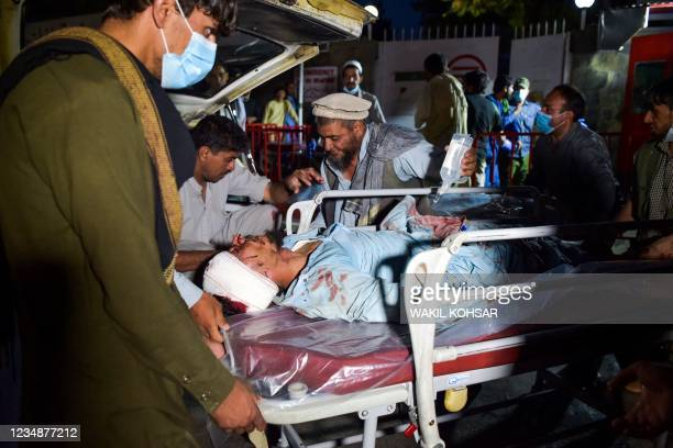 Graphic content / Medical and hospital staff bring an injured man on a stretcher for treatment after two blasts, which killed at least five and...