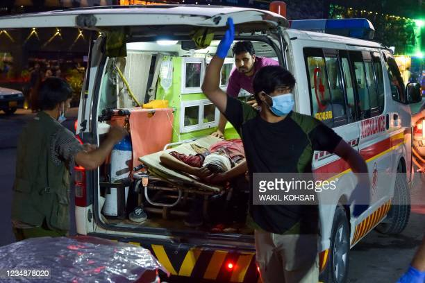 Graphic content / Medical staff bring an injured man to a hospital in an ambulance after two powerful explosions, which killed at least six people,...