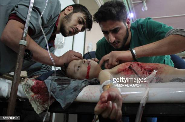 Graphic content / Medics treat a wounded child at a makeshift clinic following reported shelling by Syrian government forces in the rebelheld town of...