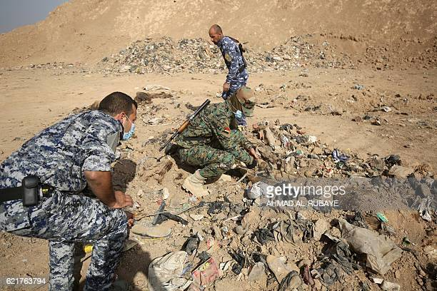Graphic content / Member of the Iraqi forces check a mass grave they discovered in the Hamam alAlil area on November 7 2016 after they recaptured the...