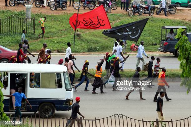 Graphic content / Members of Islamic Movement of Nigeria wave flags and chant slogans as they take part in a demonstration to protest against the...