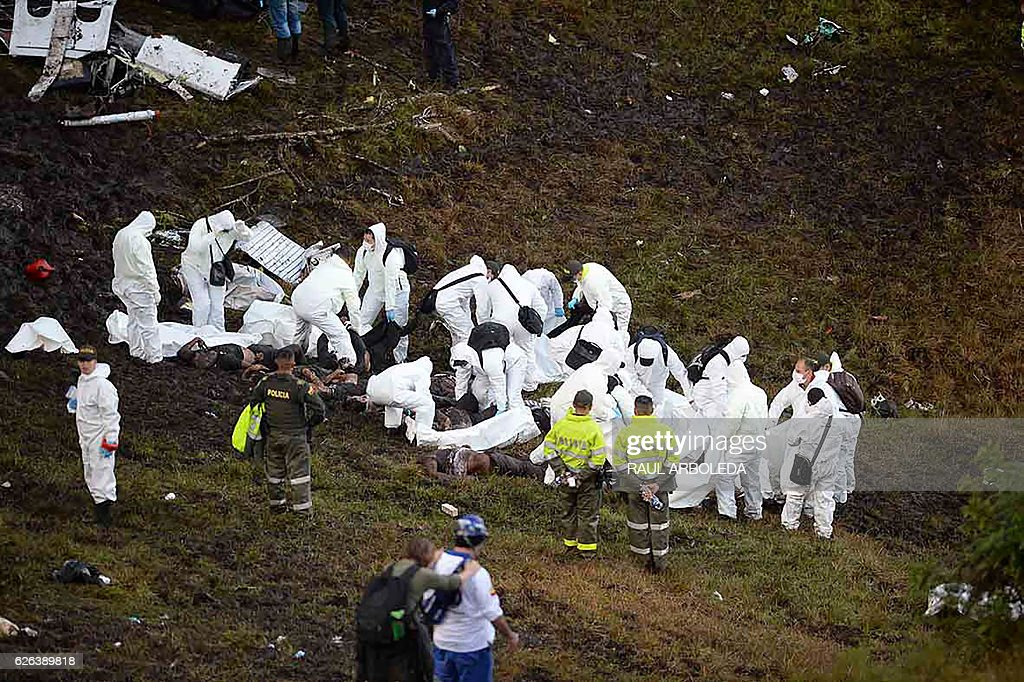 Graphic content / Members of the forensics team recover the bodies of victims of the LAMIA airlines charter plane crash in the mountains of Cerro Gordo, municipality of La Union, on November 29, 2016. A charter plane carrying the Chapecoense Real football team crashed in the mountains in Colombia late Monday, killing as many as 75 people, officials said. / AFP / RAUL