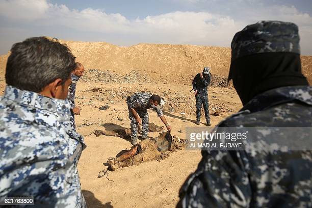 Graphic content / Members of the Iraqi forces check a body they pulled from a mass grave they discovered in the Hamam alAlil area on November 7 2016...
