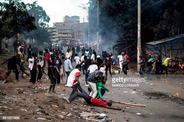 Graphic content / Members of the Kikuyu ethnic group residents of Mathare try to recover the body of a man who was beaten and stoned to death by...