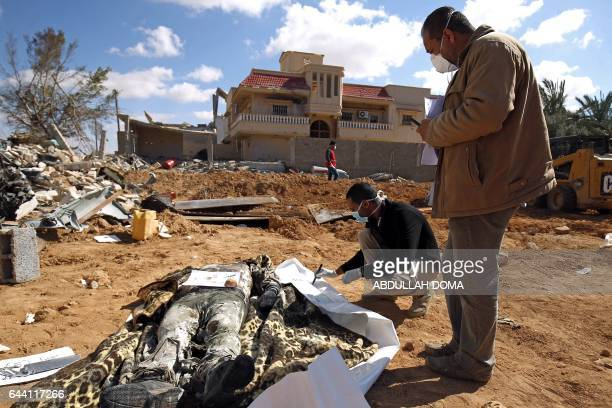 Graphic content / Members of the Libyan Red Crescent examine an unidentified bodies they exhumed from a mass grave of people killed during fighting...