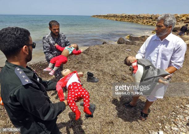 Graphic content / Members of the Libyan security forces and a civilian carry the bodies of babies as migrants who survived the sinking of an...