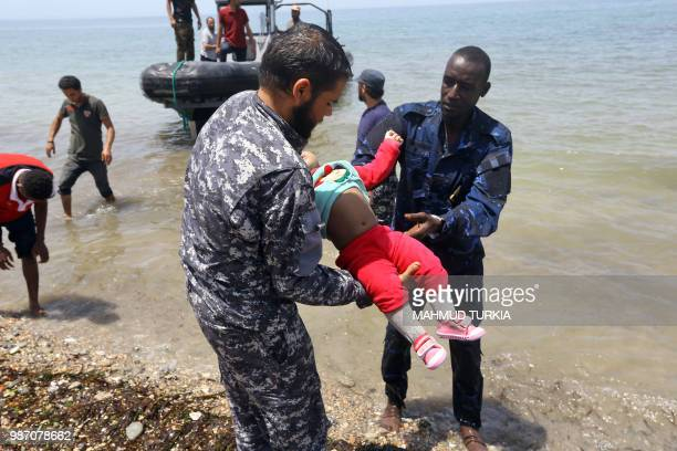 Graphic content / Members of the Libyan security forces carry the body of a baby as migrants who survived the sinking of an inflatable dinghy boat...