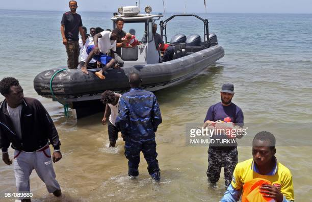 Graphic content / Members of the Libyan security forces carry the bodies of babies as migrants who survived the sinking of an inflatable dinghy boat...