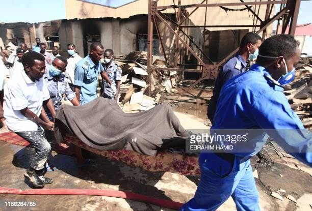 Graphic content / Members of the Sudanese Civil Defence transport the bodies of victims of a fire at a tile manufacturing unit in an industrial zone...
