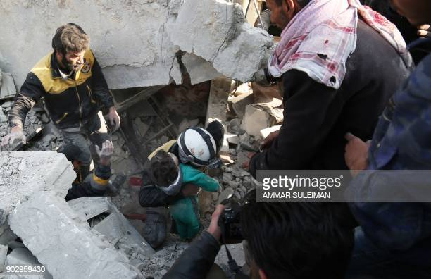 Graphic content / Members of the Syrian Civil Defence and civilians rescue a child from under the rubble following a reported air strike on the...