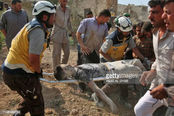 Graphic content / Members of the Syrian Civil Defence evacuate a young victim following a reported air strike by progovernment forces on the village...