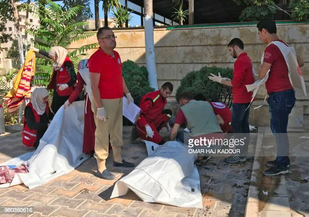 Graphic content / Members of the Syrian Civil Defence wrap in bags the bodies of victims killed in a double explosion in the northern rebelheld city...