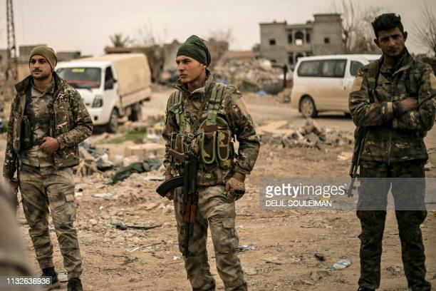 Graphic content / Members of the Syrian Democratic Forces stand in the village of Baghouz in Syria's eastern Deir Ezzor province near the Iraqi...