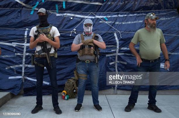 Graphic content / Men armed with automatic weapons stand in front of the State Capitol building as Trump supporters and members of the alt-right...