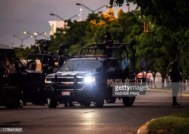 Graphic content / Mexican police patrol in a street of Culiacan, state of Sinaloa, Mexico, on October 17 after heavily armed gunmen in four-by-four...