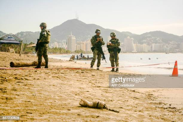Graphic content / Mexican soldiers guard the crime scene where a human arm was found in the beach of Hornos in the tourist city of Acapulco Guerrero...