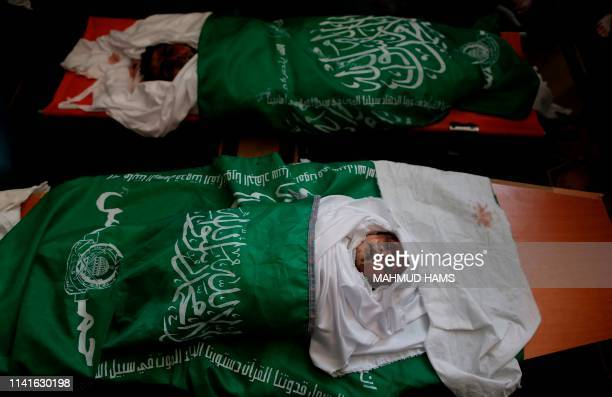 Graphic content / Mourners gather around the bodies of Palestinians who were killed in Israeli strikes the previous day during a funeral ceremony at...
