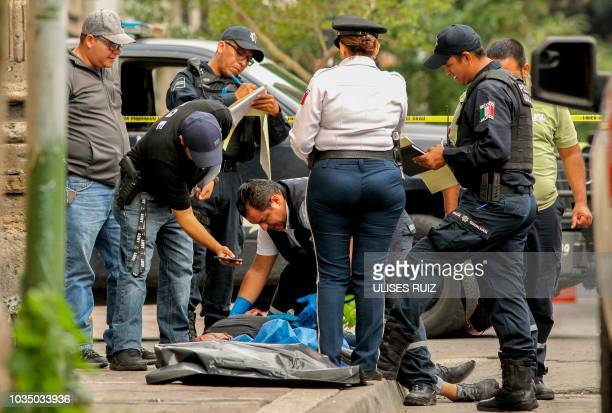 Graphic content / Municipal police members and forensic personnel work at the crime scene after a person was murdered in Guadalajara downtown jalisco...