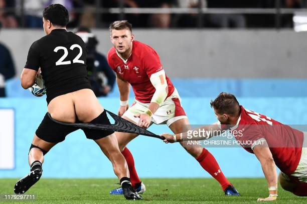 Graphic content / New Zealand's centre Anton Lienert-Brown has his shorts pulled by Wales' wing Hallam Amos during the Japan 2019 Rugby World Cup...