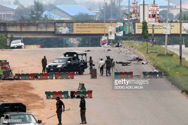Graphic content / Nigerian soldiers stand guard as they surround the dead bodies of members of Islamic Movement of Nigeria following violent clashes...