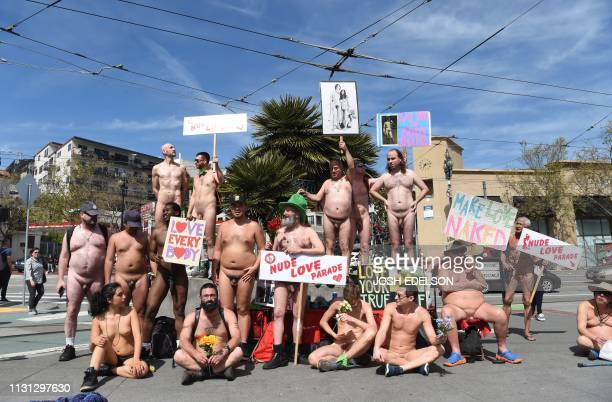 Graphic content / Nudists hold up signs at an intersection before the start of the Nude Love Parade in San Francisco California on March 17 2019...