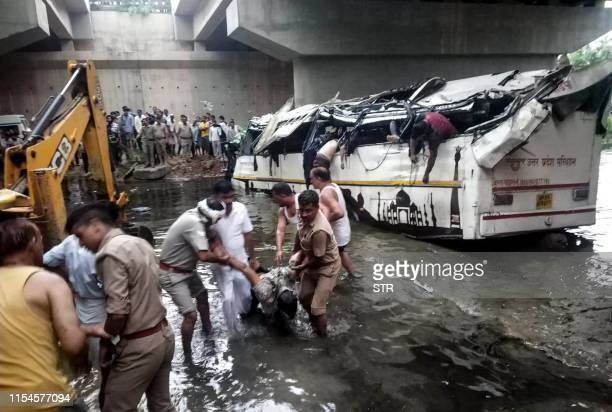 Graphic content / Onlookers and Indian police retrieve dead bodies from the crumpled remains of a bus that crashed on the DelhiAgra expressway near...