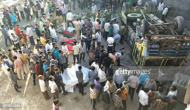 Graphic content / Onlookers gather around the bodies of passengers who had been travelling in a truck that plunged off a bridge in Bhavnagar district...