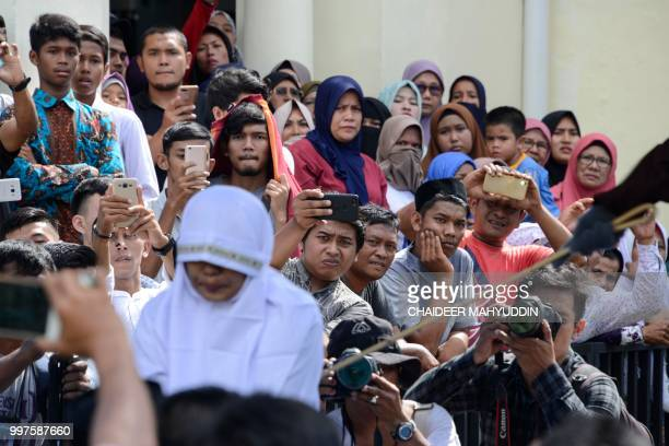 Graphic content / Onlookers watch as a member of Indonesia's Sharia police whips a nonMuslim woman for trading alcohol during a public caning...