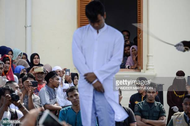 Graphic content / Onlookers watch as a member of Indonesia's Sharia police whips a man accused of having gay sex during a public caning ceremony...