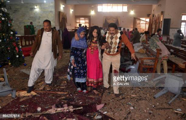 Graphic content / Pakistani Christians assist an injured worshipper after suicide bombers attacked a Methodist Church in Quetta on December 17 2017...