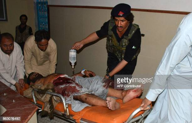 Graphic content / Pakistani men shift an injured victim into a hospital in Quetta on October 19 after an explosion in Balochistan's Mastung District...