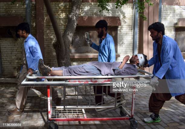 Graphic content / Pakistani paramedics carry an injured blast victim at a hospital following a bomb blast at a fruit market in Quetta on April 12...