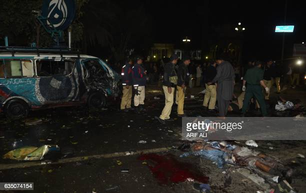 Graphic content / Pakistani police officials and volunteers move the bodies of victims at the site of a bomb explosion in Lahore on February 13 2017...