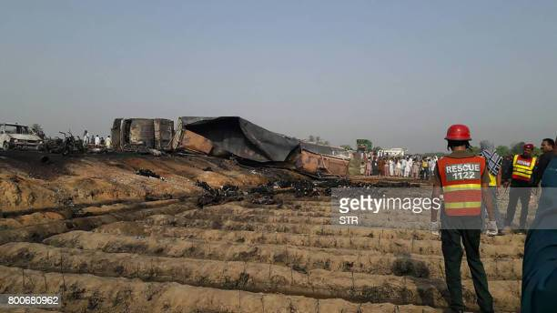 Graphic content / Pakistani rescue workers gather near burnt bodies after an oil tanker caught fire following an accident on a highway near the town...