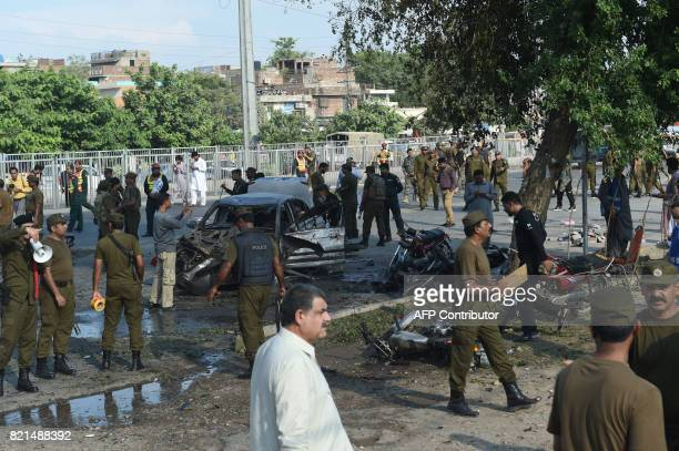 Graphic content / Pakistani security officals inspect the site after an explosion in Lahore on July 24 2017 An explosion killed at least 20 people...