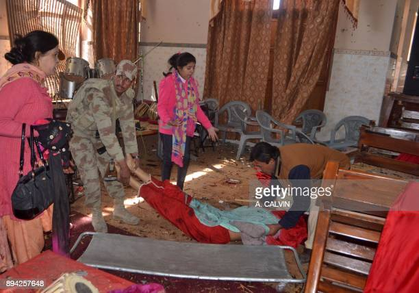 Graphic content / Pakistani security personnel and volunteers shift the body of a victim after suicide bombers attacked a Methodist Church in Quetta...