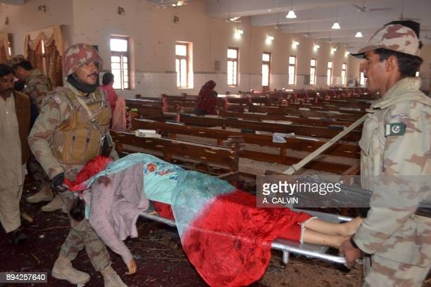 Graphic content / Pakistani security personnel carry the body of a victim after suicide bombers attacked a Methodist Church in Quetta on December 17...