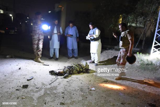 Graphic content / Pakistani security personnel gather beside the body of a militant following an attack on the paramilitary Frontier Corps office in...