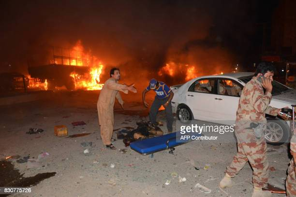 Graphic content / Pakistani soldiers and volunteers attempt to move a victim's body after a blast in Quetta on August 12 2017 A powerful blast has...