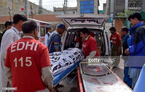 Graphic content / Pakistani volunteers carry the dead body of a blast victim onto an ambulance outside an hospital following a bomb blast at a fruit...