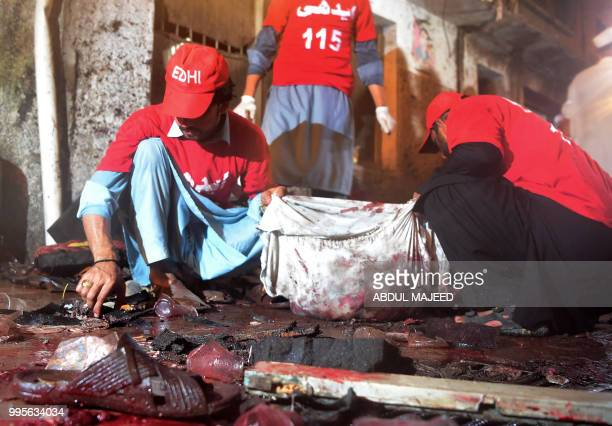 Graphic content / Pakistani volunteers collect human remains from the site after a suicide bombing at an election rally in Peshawar on July 10 2018 A...